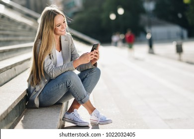 Beautiful young caucasian woman looking at her smartphone and smiling in urban background. Blond girl wearing casual clothes sitting on stairs.