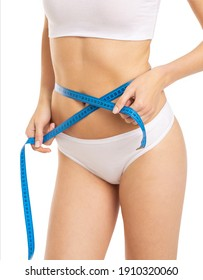 beautiful young caucasian woman measuring her figure size with tape measure. Womans holding centimeter and measuring the size of thin body