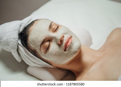 Beautiful young Caucasian woman with a natural facial mask on her face lying on the massage table.