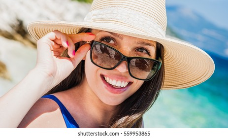 Beautiful young caucasian woman obliviously enjoying the mediterranean summer sun on the beach with straw hat and sunglass to defend herself against the harmful rays