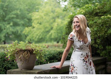 Beautiful young Caucasian woman poses in white floral print dress in front of home - laughing as she looks over shoulder and smiling