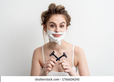 Beautiful young caucasian woman with shaving foam on her face and two razors in her hands on white background