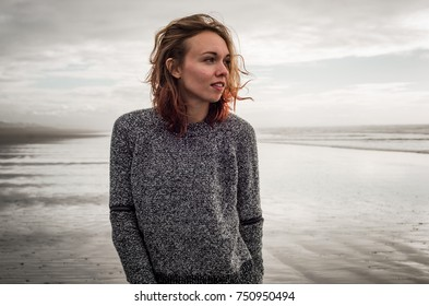 Beautiful young caucasian woman with short brown brunette hair stands on a sandy beach looking away from the camera at the Pacific Ocean on the Northern California coast