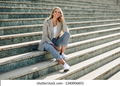 Beautiful young caucasian woman smiling in urban background. Blond girl wearing casual clothes in the street. Female with elegant jacket and blue jeans sitting on stairs.