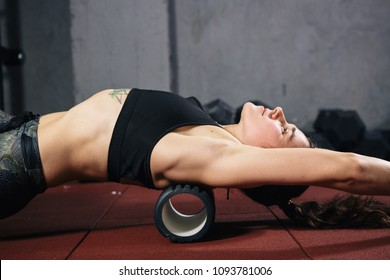 Beautiful young caucasian woman sportswoman uses a foam roller massager for relaxation, stretching muscles and back pain. Girl in the gym green sneakers T-shirt and tights.