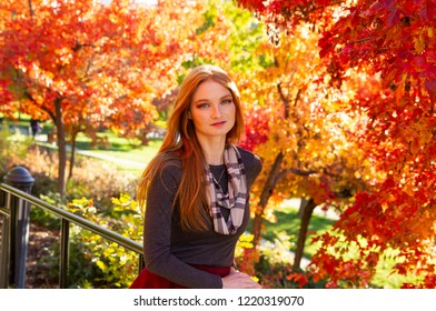 A beautiful young Caucasian woman standing in front of colorful autumn leaves in a park. Conceptual image of autumn, and appreciating the beauty of season.