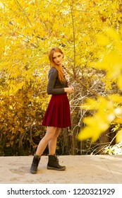 A beautiful young Caucasian woman, standing and being surrounded by beautiful yellow autumn colored leaves. Conceptual image for autumn an beauty.