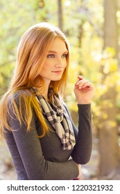 A beautiful young Caucasian woman standing in front of beautiful autumn colored leaves in a park. Conceptual image for autumn, or appreciating the beauty of season.