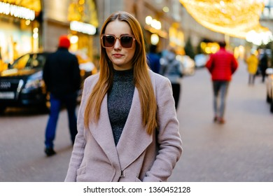 Beautiful young caucasian woman standing next standing in luxury district in city downtown. Stylish female model wearing sunglasses photographed in luxury district.