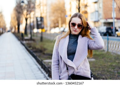 Beautiful young caucasian woman walking along the street in the city. Stylish female model running her hands through hair walking on city street.