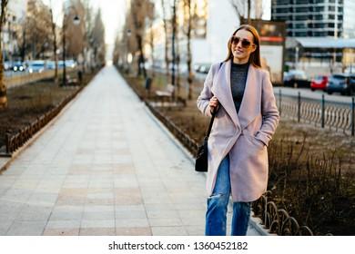 Beautiful young caucasian woman walking along the street in the city. Stylish female model wearing sunglasses walking on city street.
