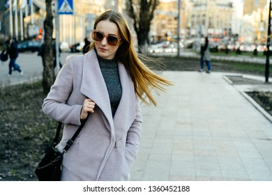 Beautiful young caucasian woman walking along the street in the city. Stylish female model swinging her hair in sunglasses walking on city street.