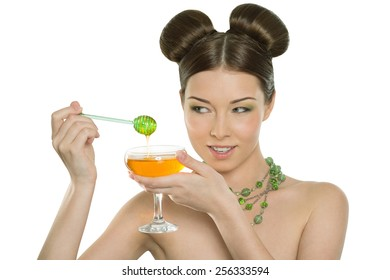 Beautiful young cheerful girl holding honey