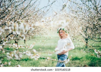 Beautiful young cheerful pregnant woman in wreath of flowers on head touching belly while walking in spring tree garden. Beauty  People Lifestyle concepts. Happy mom in waiting for baby!