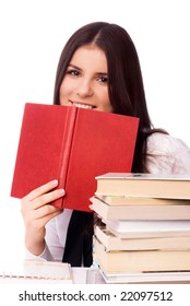 beautiful young cheerful student sitting by the table with books and doing homework