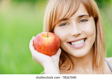 Beautiful young cheerful woman with red big apple, against green summer garden.