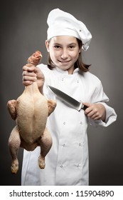 beautiful young chef  holding a chicken on gray background