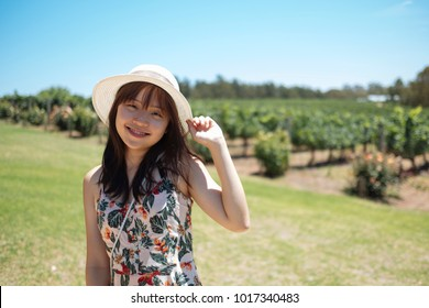 Beautiful young chinese asian long hair lady with hat and floral dress standing at one of the many wineries at Swan Valley. Popular for wedding and corporate functions. Daily wine tasting tours.