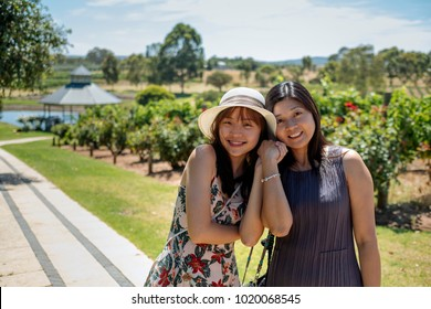 Beautiful young chinese asian long hair mother and daughter with hat and floral dress standing at one of the many wineries. Popular for wedding and corporate functions. Daily wine tasting tours.