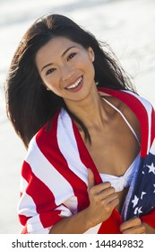 Beautiful young Chinese Asian woman laughing wearing bikini and wrapped in American flag towel on a sunny beach