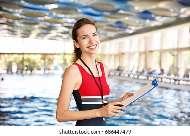 Beautiful young coach with clipboard near swimming pool