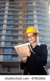 Beautiful young construction engineer/architect using tablet computer at construction site