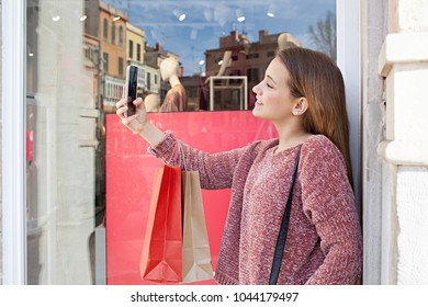 Beautiful young consumer woman shopping in fashion store street with manikins, smiling taking selfies with smart phone, outdoors. Teenager using technology, networking recreation lifestyle leisure.