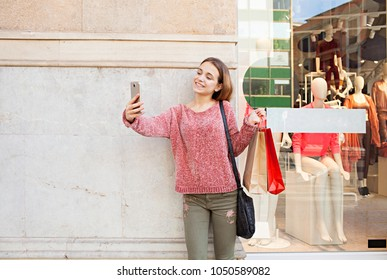 Beautiful young consumer woman shopping in fashion store street with wall space, smiling taking selfies with smart phone, outdoors. Teenager using technology, networking recreation lifestyle leisure.