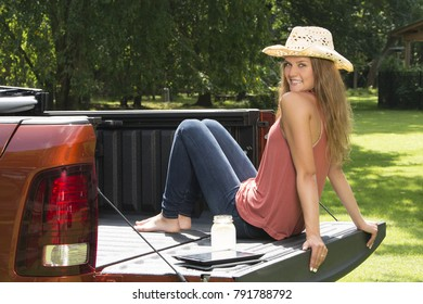 Beautiful young country girl poses with jar of lemonade in back of pickup truck on farm wearing blue jeans and using tablet computer