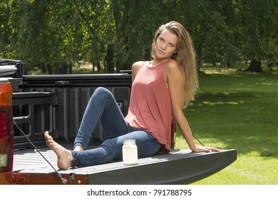 Beautiful young country girl poses with jar of lemonade in back of pickup truck on farm wearing blue jeans