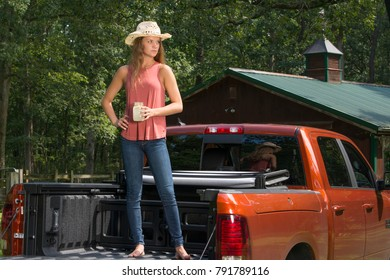Beautiful young country girl standing int the bed of a pickup truck on farm wearing blue jeans