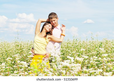 beautiful young couple among the flowers in a sunny day