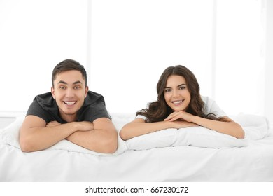 Beautiful young couple in bed at home