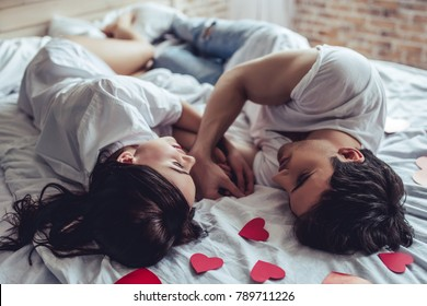 Beautiful young couple in bedroom is lying on bed with red hearts nearby. Enjoying spending time together. Celebrating Saint Valentines Day.