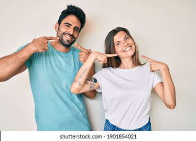 Beautiful young couple of boyfriend and girlfriend together smiling cheerful showing and pointing with fingers teeth and mouth. dental health concept.