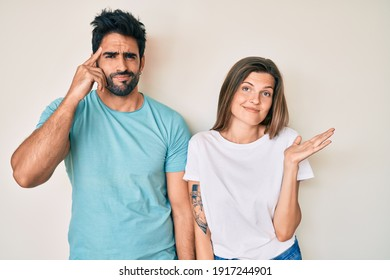 Beautiful young couple of boyfriend and girlfriend together confused and annoyed with open palm showing copy space and pointing finger to forehead. think about it.