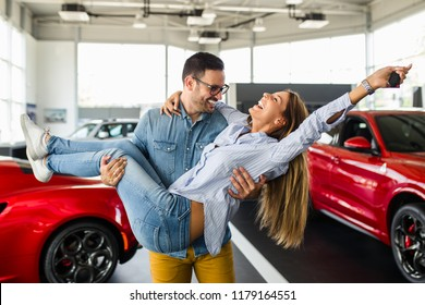 Beautiful young couple at car showroom exited because of buying a new car.