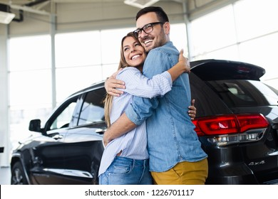 Beautiful young couple at car showroom choosing a new car to buy.