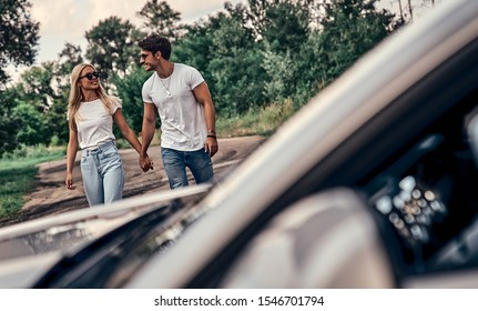 Beautiful young couple in casual clothes near sport car.