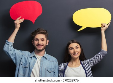Beautiful young couple in casual clothes is holding colorful speech bubbles, looking at camera and smiling, standing against blackboard