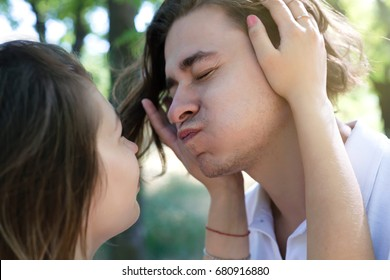 Beautiful young couple in casual clothes is looking at each other, smiling and going crazy.Close up portrait of happy young couple in love embracing .Outdoor Portrait Of Romantic Young Couple In Park
