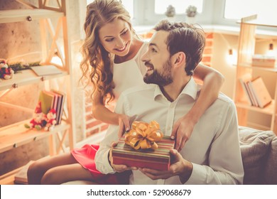 Beautiful young couple is celebrating at home. Pretty girl is giving her boyfriend a gift box