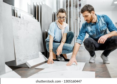 Beautiful young couple choosing big granite tiles for their house repairment in the building shop