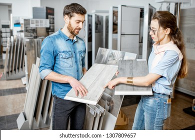 Beautiful young couple choosing ceramic tiles for their house repairment in the building shop