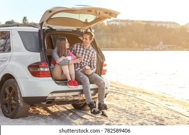 Beautiful young couple with coffee sitting in car trunk near river