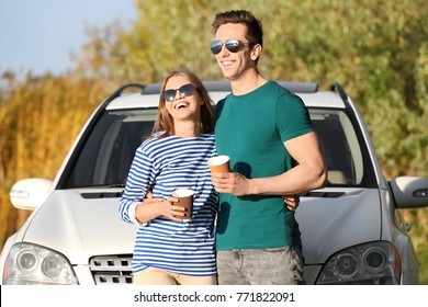 Beautiful young couple with coffee standing near car outdoors