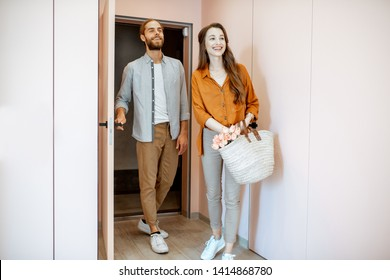 Beautiful young couple coming home, walking together in the pink corridor of the modern apartment