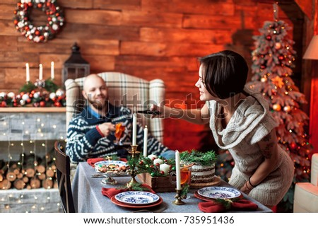 Beautiful young couple cover the table in preparation for Christmas dinner in the beautifully decorated New Year interior with Christmas tree