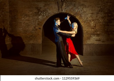 Beautiful young couple dancing tango in the twilight.