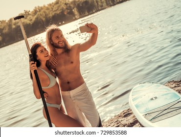 Beautiful young couple is doing selfie using a smart phone other and smiling; going to stand up paddle boarding